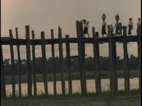 Women and children cross a bridge Stock Video Footage