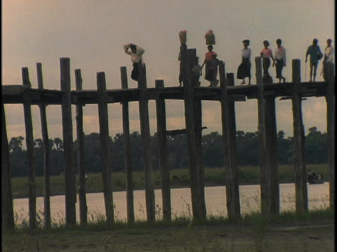 Women and children cross a bridge Footage