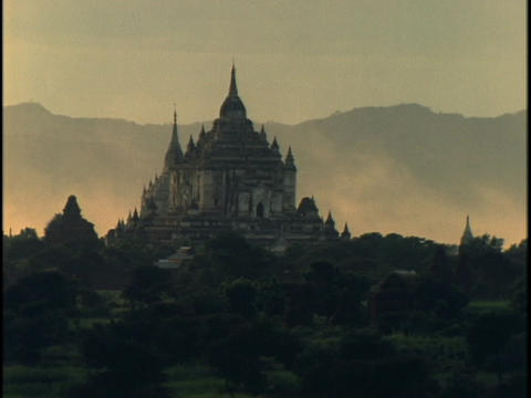 Fog rolls behind a majestic, ancient Buddhist temple in Burma Footage
