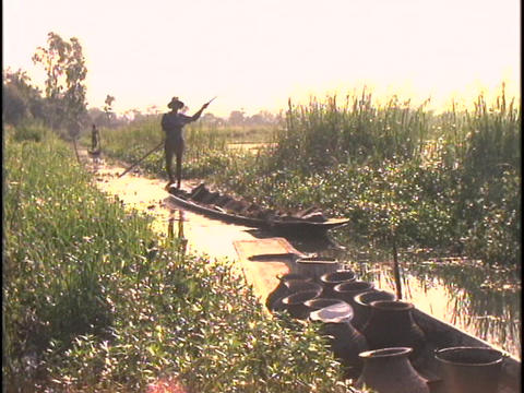 A man in silhouette rows a canoe on Inle Lake in Burma Stock Video Footage