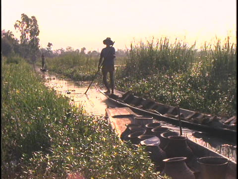 A man in silhouette rows a canoe on Inle Lake in Burma Footage