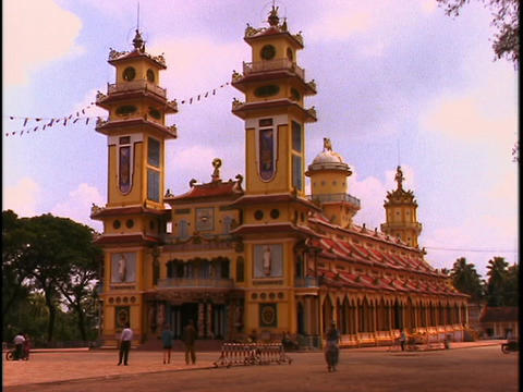 Pedestrians and bicyclists move past the Cao Dai temple in South Vietnam Footage