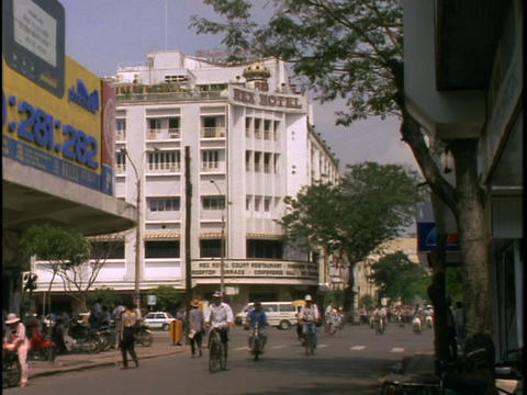 Bicyclists cruse down a busy street of Saigon, Ho Chi... Stock Video Footage