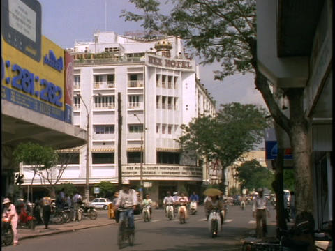 Bicyclists cruse down a busy street of Saigon, Ho Chi Minh City, Vietnam Footage