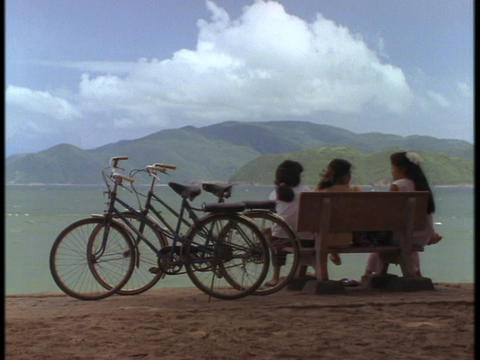 Vietnamese schoolgirls sit on bench overlooking the South... Stock Video Footage