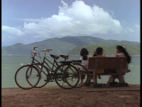 Vietnamese schoolgirls sit on bench overlooking the South China Sea Footage