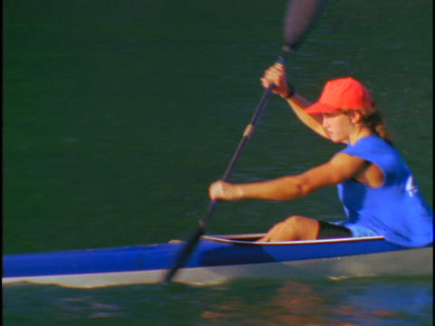 A woman kayaker rows quickly through the water Footage