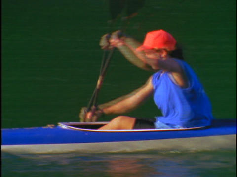 A woman kayaker rows quickly through the water Stock Video Footage
