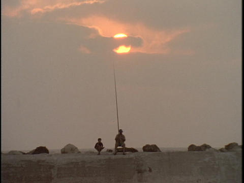 A father and son fish together during golden-hour Stock Video Footage