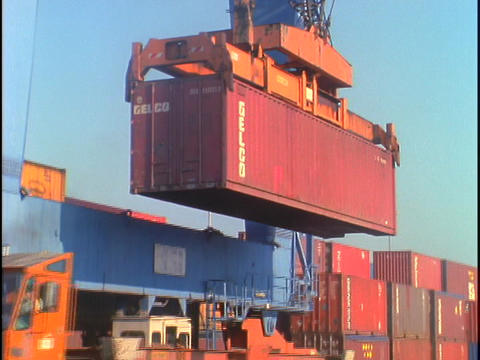 A crane unloads a shipping container from a truck Footage