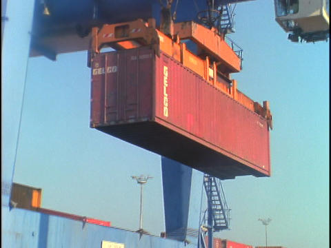 A crane unloads a shipping container from a truck Stock Video Footage