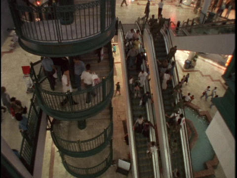 Shoppers ride escalators and climb stairs in a mall Stock Video Footage