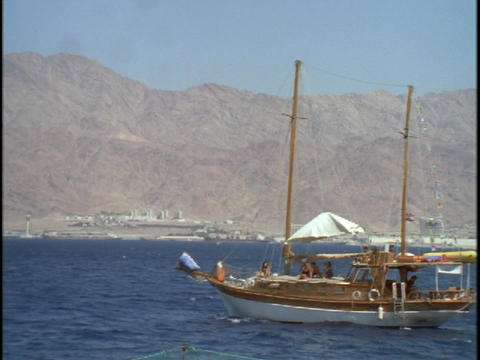A sail boat sails near the desert Footage