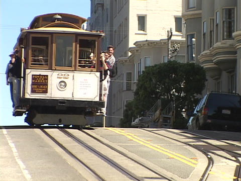 A cable car comes over the hill in San Francisco, California Live Action