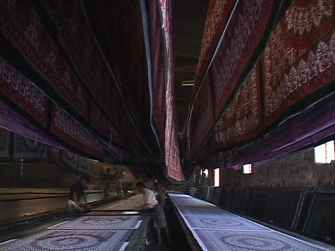 Workers arrange rugs in a carpet factory Stock Video Footage