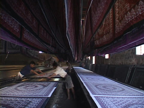 Workers arrange rugs in a carpet factory Footage