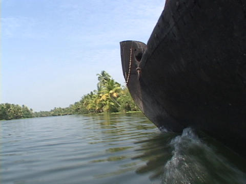 A riverboat floats through a jungle river Stock Video Footage