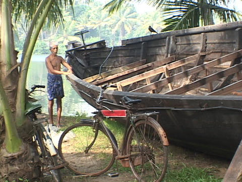An elderly man pats a boat beside the river Footage