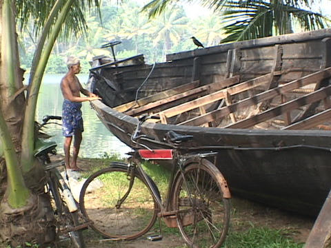 An elderly man pats a boat beside the river Stock Video Footage