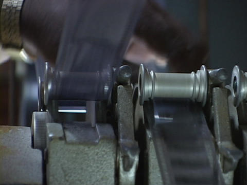 Hands control film as it feed through a roller Stock Video Footage