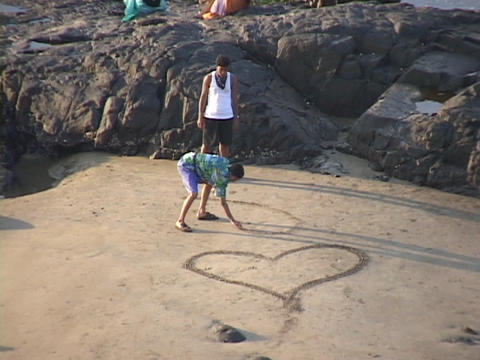 Boys draw hearts in the sand Stock Video Footage