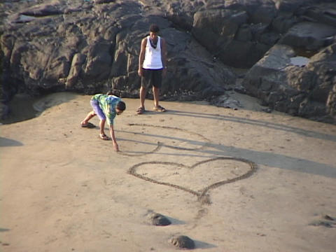 Boys draw hearts in the sand Live Action