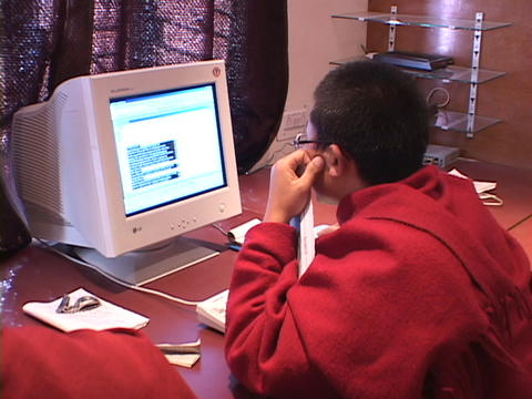 A Buddhist monk works on a computer Footage