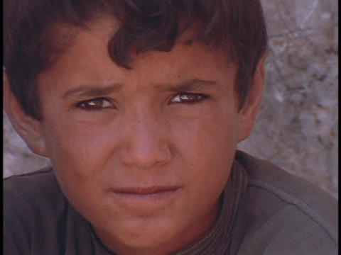 A young Arab boy rubs his eyes Stock Video Footage