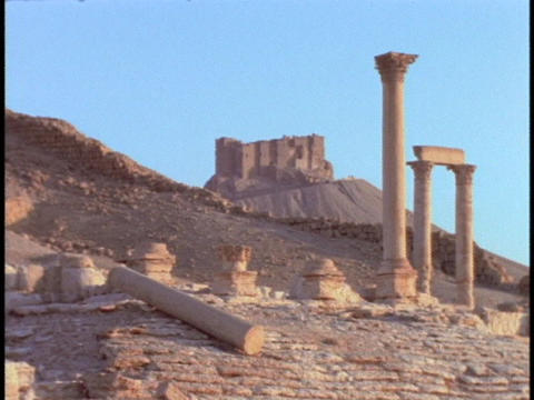 Roman style pillars stand in partial ruin in a desert Stock Video Footage