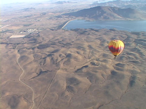 A hot air balloon flies over the desert Stock Video Footage