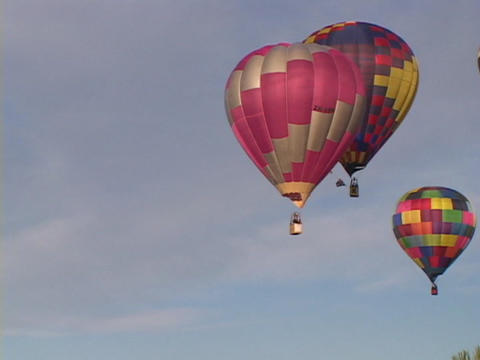 Colorful hot air balloons float through the sky Stock Video Footage