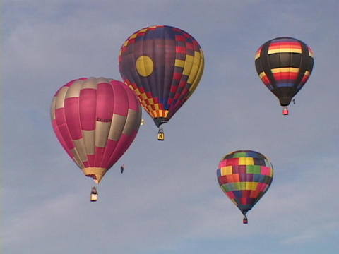 Colorful hot air balloons float through the sky Footage