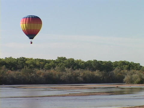 A hot air balloon floats over a forest and river Stock Video Footage