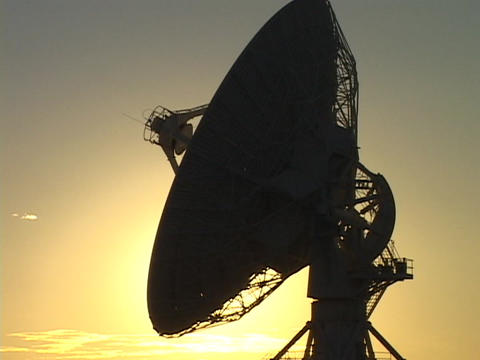 A satellite dish stands silhouetted by the sun Stock Video Footage