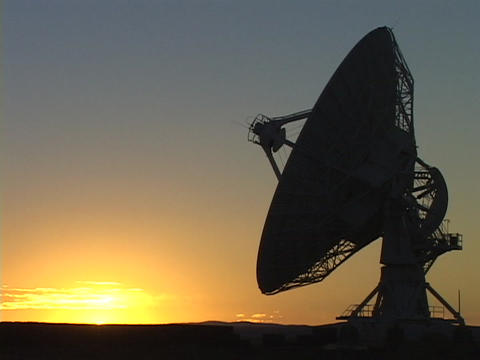 The sun sits on the horizon behind a satellite dish Footage