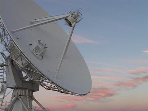 A satellite dish slowly moves before a colorful sky in New Mexico Footage
