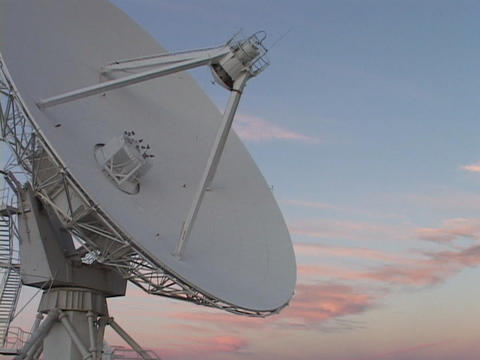 A satellite dish slowly moves before a colorful sky in... Stock Video Footage
