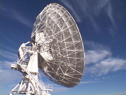 A satellite dish sits before a brilliant blue sky in New Mexico Footage
