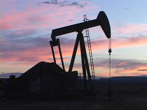 A pumping oil well stands in silhouette against colorful sky Stock Video Footage