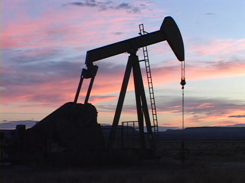 A pumping oil well stands in silhouette against colorful sky Footage
