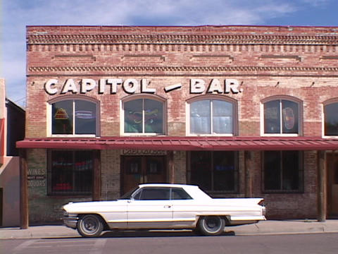 A vintage Cadillac stands parked in front of the Capitol Bar Footage