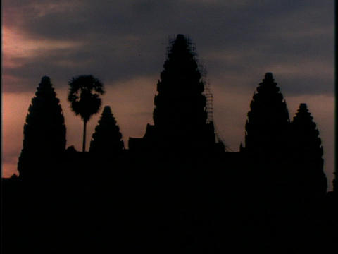 Purple clouds hang over Angkor Wat temple in Cambodia during golden hour Footage