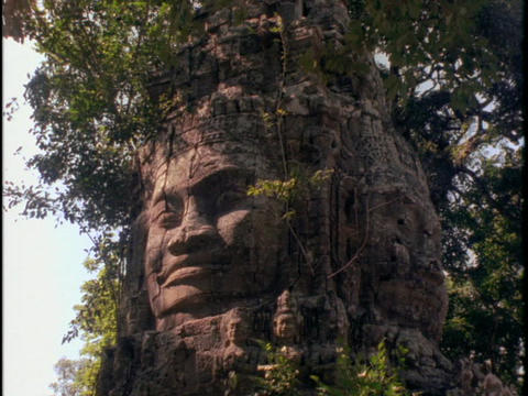 A face carved in stone watches over Angkor Wat temple in Cambodia Footage