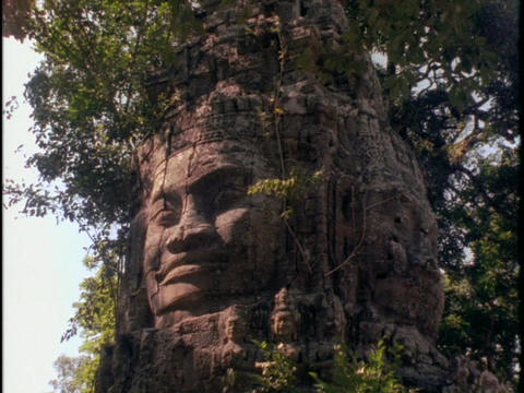 A face carved in stone watches over Angkor Wat temple in... Stock Video Footage