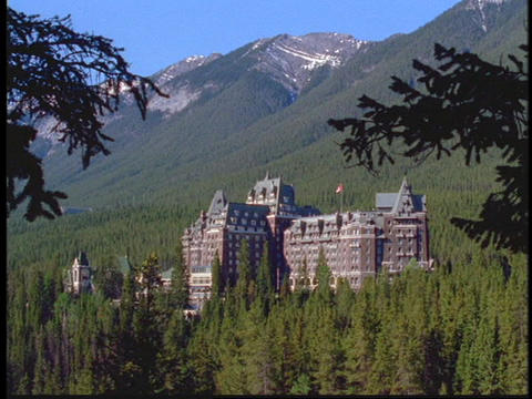 A large hotel sits at the base of the Canadian Rockies Stock Video Footage