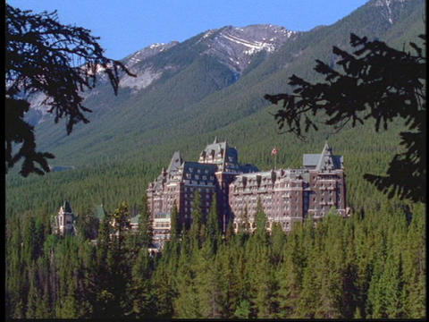 A large hotel sits at the base of the Canadian Rockies Footage