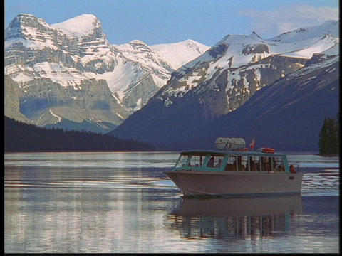 A tour boat travels on a clear blue lake in the Canadian... Stock Video Footage