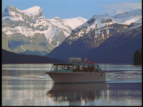 A tour boat travels on a clear blue lake in the Canadian Rockies Footage