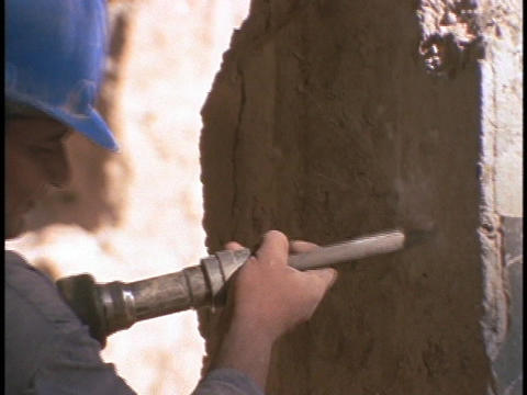 A construction worker drills holes Stock Video Footage