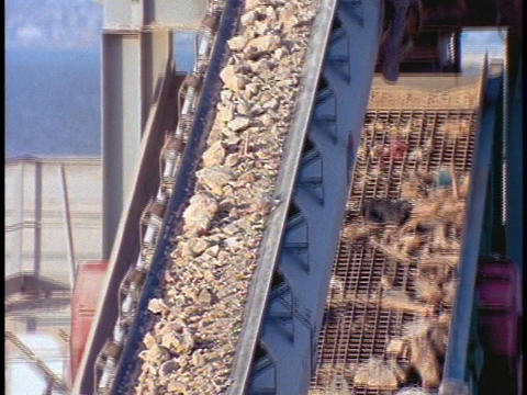 A conveyor belt moves rubble at a construction site Footage